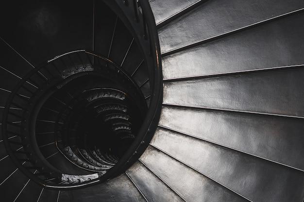 Оттенки серого, вид сверху на винтовую лестницу - концепция загадки Бесплатные Фотографии