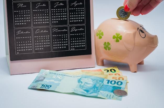 経済、カレンダー、貯金箱、本物のブラジルの紙幣の素晴らしいコンセプト。貯金箱にコインを挿入する女性の手。 Premium写真