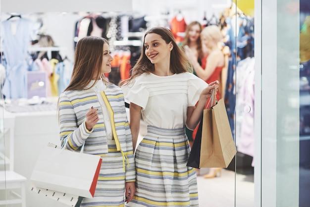 ショッピングに最適な日。衣料品店を歩きながら笑顔でお互いを見つめるバッグを持つ2人の美しい女性 無料写真