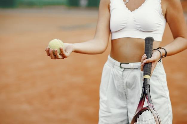 Ottima giornata per giocare! giovane donna allegra in maglietta. donna che mantiene racchetta da tennis e palla. Foto Gratuite