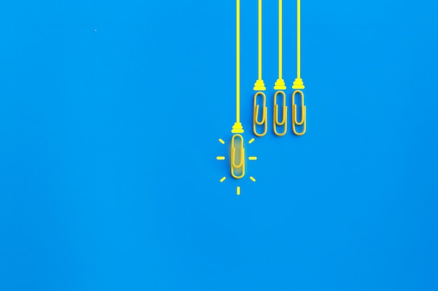 Great ideas concept with paperclip,thinking,creativity,light bulb on blue background,new ideas concept. Premium Photo
