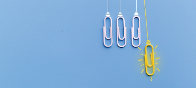 Great ideas concept with paperclip thinking creativity light bulb on blue background Premium Photo