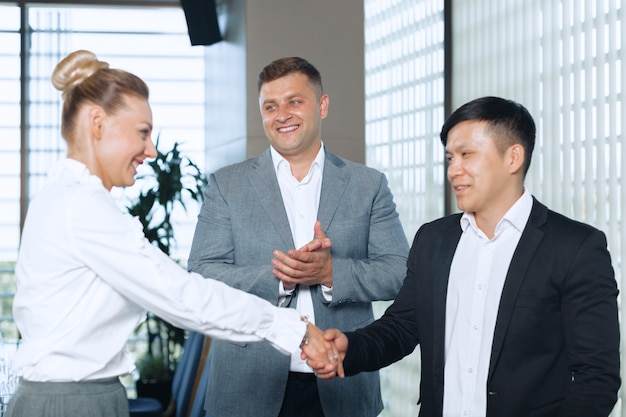 Great job! two cheerful business people shaking hands Premium Photo