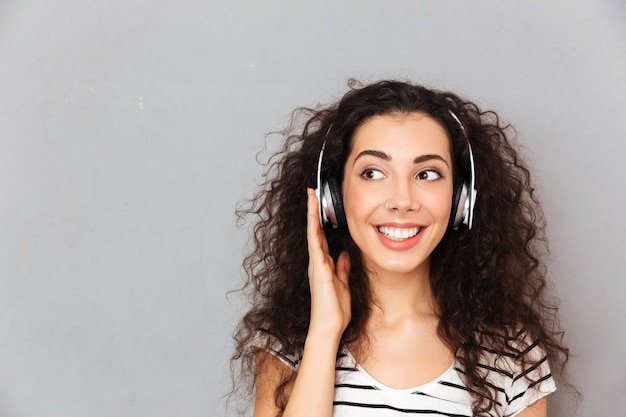Great picture of curly caucasian woman in striped t shirt in headphones enjoying music via modern device while resting Free Photo