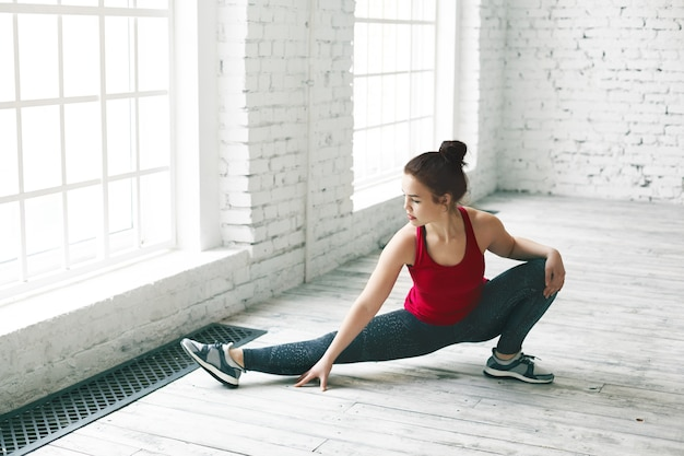 Great progress. picture of attractive young european woman doing stretches indoors, warming up leg muscles before side splits in light hall with copy space wall for your advertising content Free Photo