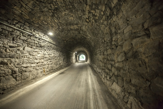 Great shot of the entrance of an old stone tunnel from the other end of an old stone tunnel Free Photo