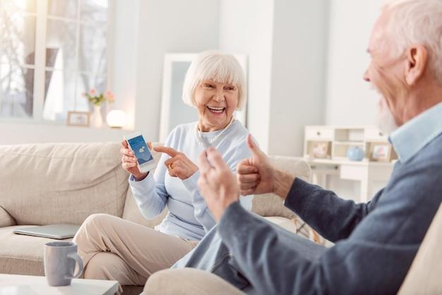 素晴らしい天気。陽気な老夫婦がリビングルームのソファに座って、天気アプリをチェックして親指を表示し、天気に満足している Premium写真