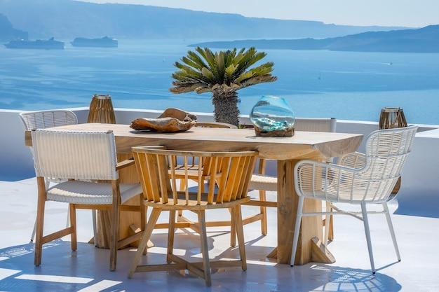 ギリシャ。サントリーニ。ティラ島。サンテラスの木製のテーブルと椅子。港にある2隻のクルーズ船 Premium写真