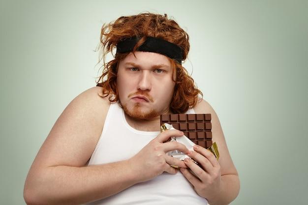 Giovane grasso obeso avido che indossa la fascia sportiva sui capelli ricci dello zenzero Foto Gratuite