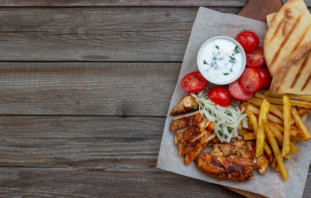 Greek dish gyros with chicken, french fries, tomatoes, onions and pita. greek cuisine. Premium Photo