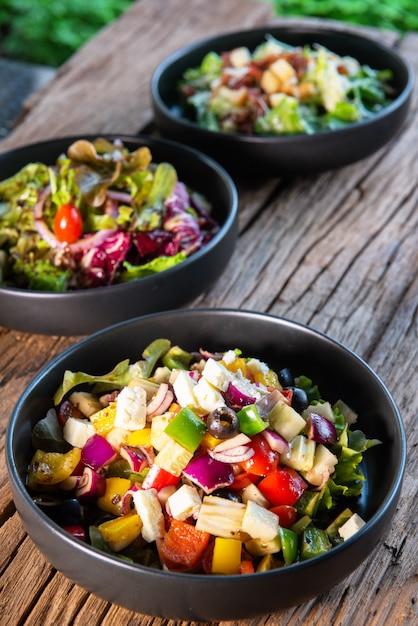 건강 샐러드, 야채 애호가를위한 나무 테이블에 검은 세라믹 그릇에 그리스 샐러드, 일본 샐러드, 시저 샐러드. 프리미엄 사진