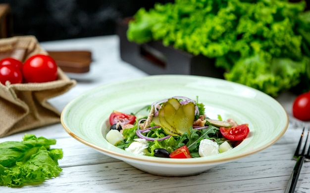 Greek salad topped with pickles Free Photo