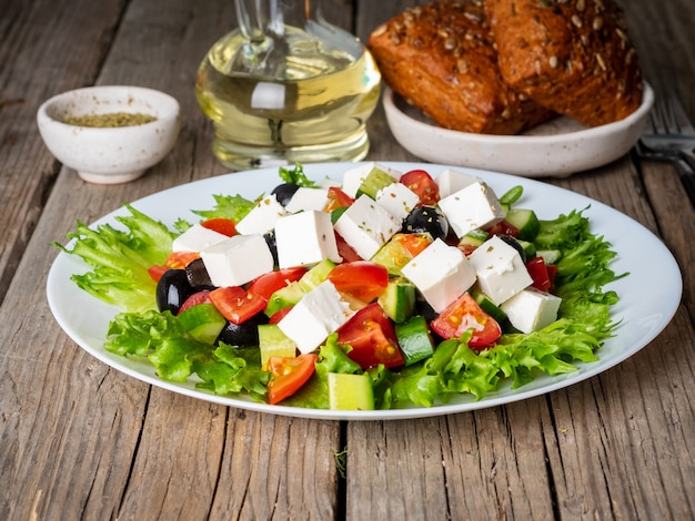 Greek salad on white plate on old rustic wooden table, side view Premium Photo