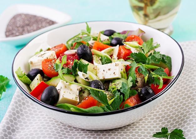 Insalata greca con cetrioli, pomodori, peperoni, lattuga, cipolla verde, formaggio feta e olive con olio d'oliva. cibo salutare. Foto Gratuite