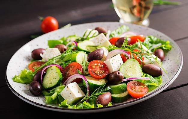Greek salad with fresh vegetables, feta cheese and kalamata olives Free Photo