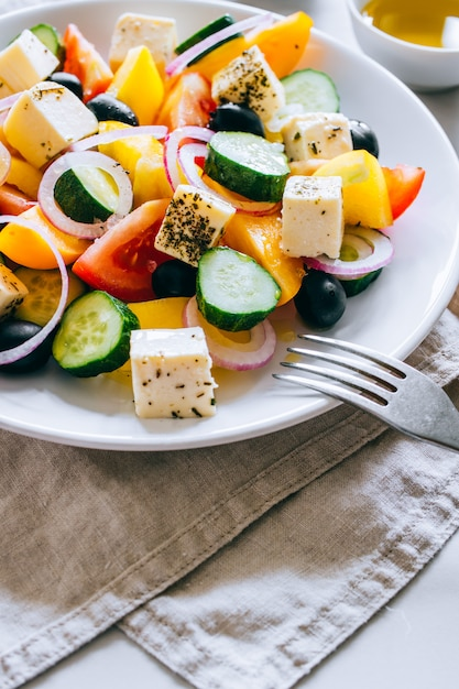Greek salad of with olive oil on marble. Premium Photo