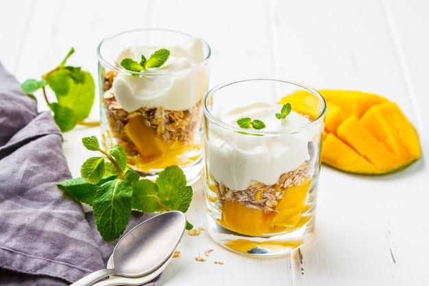 Greek yogurt mango granola parfait in a glass on white wooden background. Premium Photo