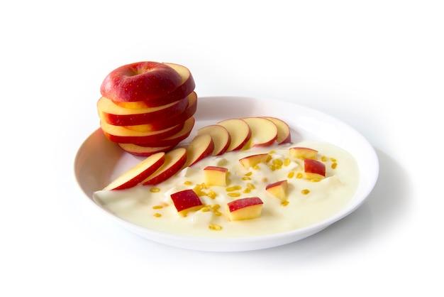 Greek yogurt original flavour with fresh slice red apple on the white plate Premium Photo