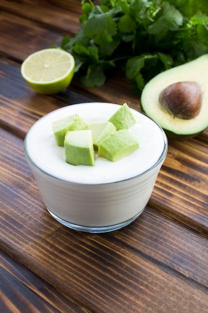 Греческий йогурт с авокадо на деревянном столе Premium Фотографии