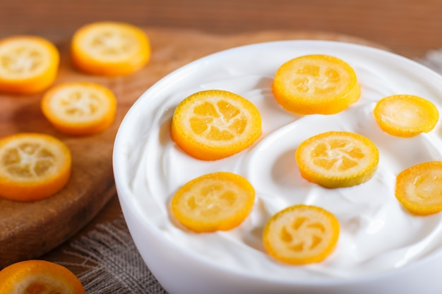 Greek yogurt with kumquat pieces in a white plate on a brown wooden background Premium Photo