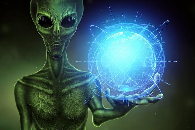 Зеленый инопланетянин, гуманоид, держит на руке голограмму земного шара. концепция нло, инопланетяне, контакт с внеземной цивилизацией. Premium Фотографии