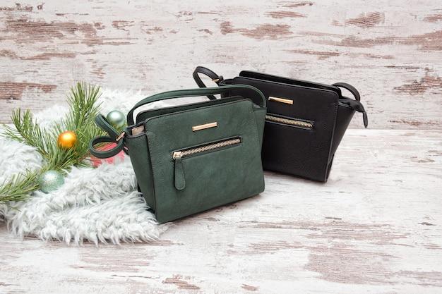 Зеленая и коричневая женская сумочка на деревянном фоне Premium Фотографии