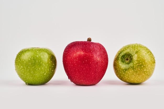Зеленые и красные яблоки на белой поверхности. Бесплатные Фотографии