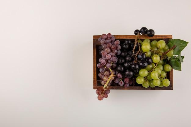 中央の木製の箱に緑と赤のブドウの房 無料写真