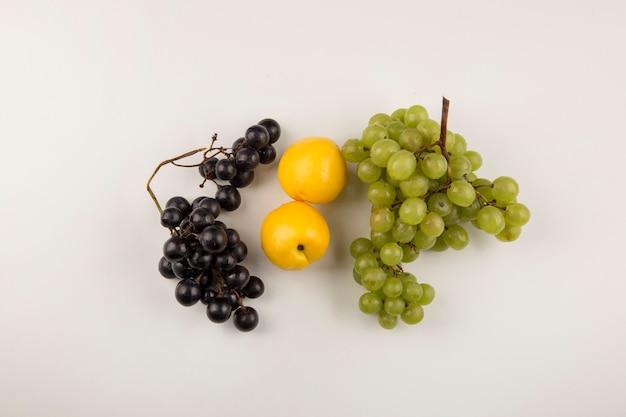 Грозди зеленого и красного винограда с желтыми персиками в центре Бесплатные Фотографии