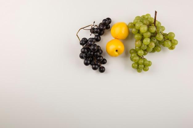Грозди зеленого и красного винограда с желтыми персиками Бесплатные Фотографии