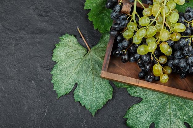 木製のトレイに緑と赤のブドウ。 無料写真