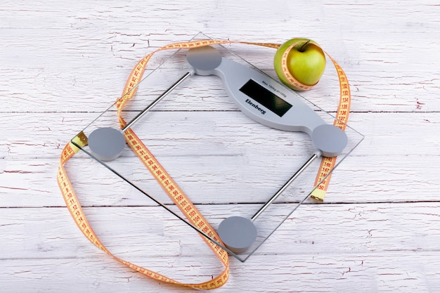 Green apple, orange  tape-measure lie on glass weighing scales Free Photo