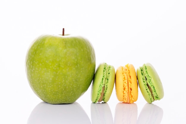 Зеленое яблоко с зеленым и желтым миндальным печеньем Бесплатные Фотографии