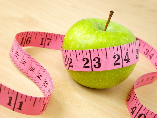 Green apple and yellow measure, healthcare and diet concept Premium Photo