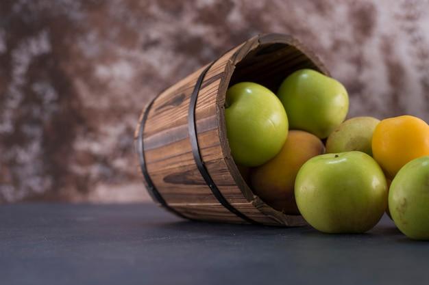 Зеленые яблоки и апельсины из деревянного ведра Бесплатные Фотографии