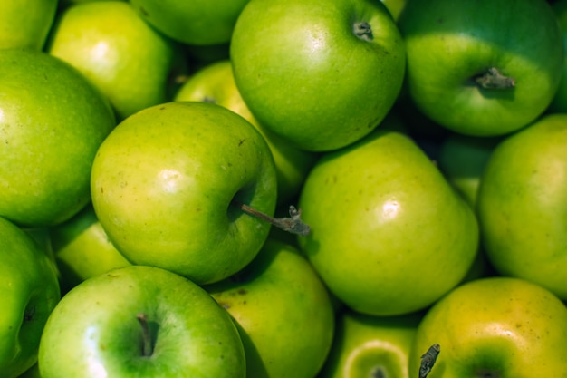 Green apples background full of oranges. fresh green apple on the market. Premium Photo