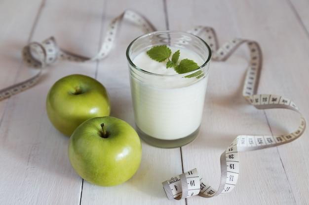 Green apples, glass of yoghurt and measure tape Premium Photo