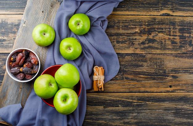 Зеленые яблоки с палочками корицы, миска даты на деревянной части в миске на деревянном и текстильном фоне Бесплатные Фотографии