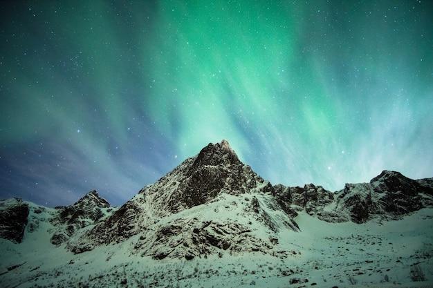Lofoten 섬의 눈 산에 녹색 오로라 보 리 얼리 스 폭발 프리미엄 사진