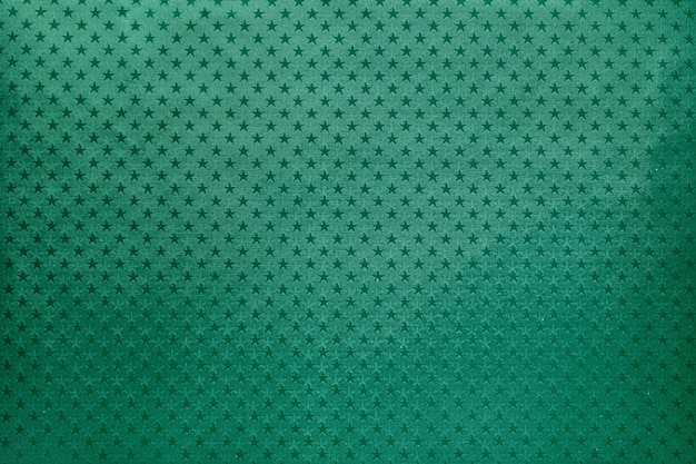 Green background from metal foil paper with a stars pattern Premium Photo