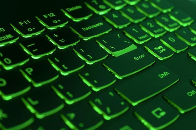 Green backlit laptop keyboard, hacking and blockchain concept Premium Photo