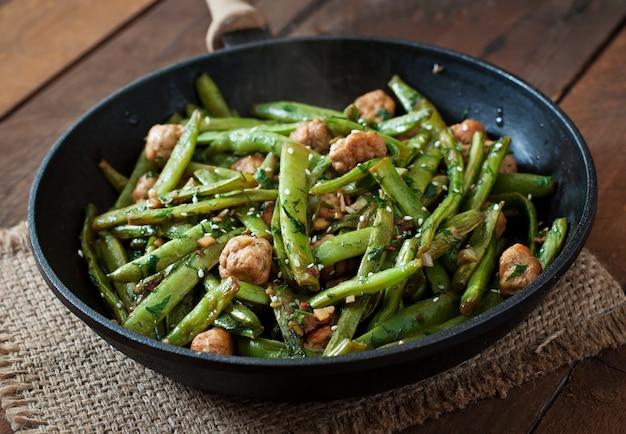 Зеленая фасоль, обжаренная с куриными фрикадельками и чесноком по-азиатски Premium Фотографии