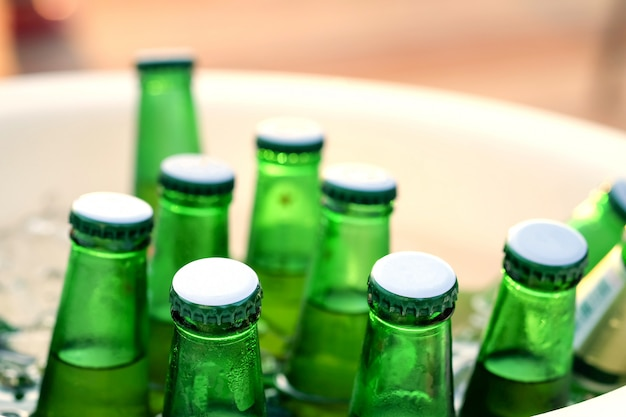 Green beer bottles are chilled in an ice bucket. Premium Photo