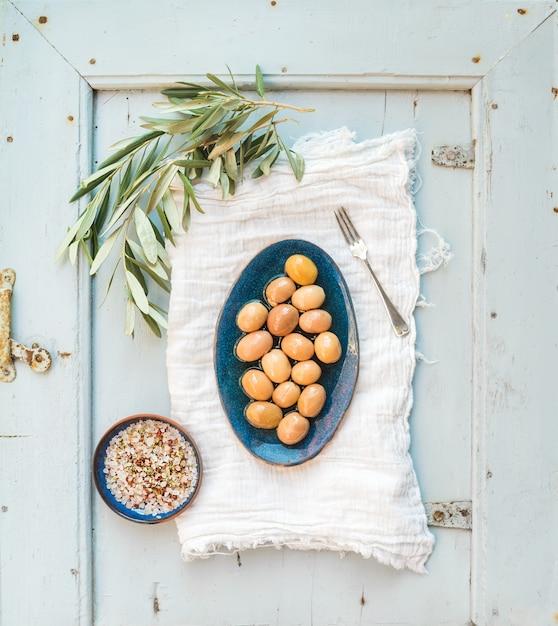 木の枝とライトブルーのテーブルの上のキッチンタオルの上のスパイスと素朴なセラミックプレートに緑の大きなオリーブ Premium写真