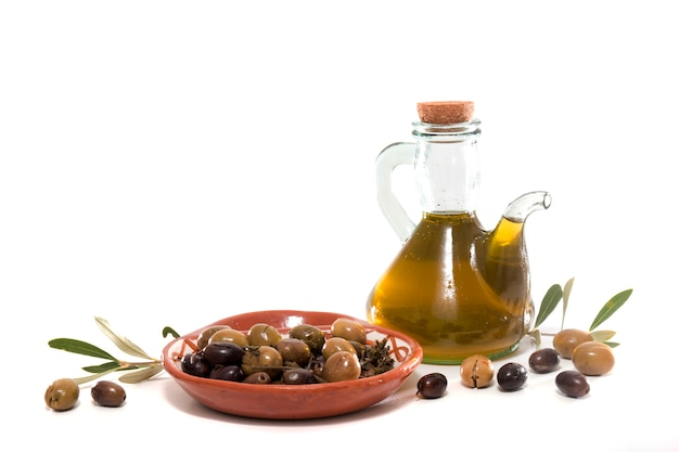 Green and black olives with olive oil bottle Premium Photo