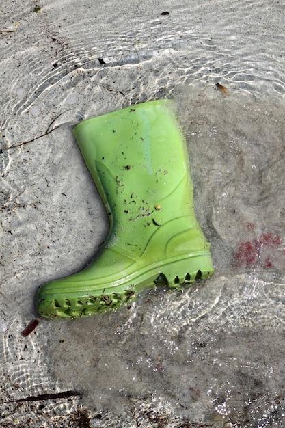 Green boots trash on beach shore pollution Premium Photo