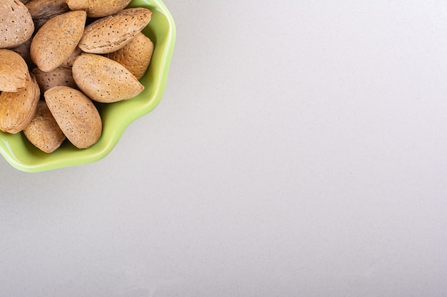 Green bowl of shelled organic almonds on white background. high quality photo Free Photo
