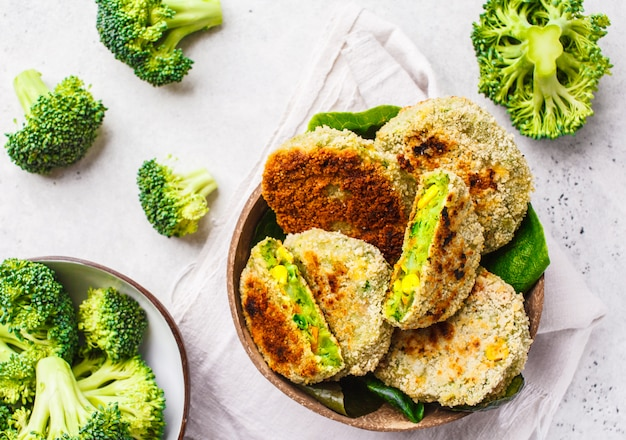 Green broccoli burgers in coconut shell dish on white background, top view. Premium Photo