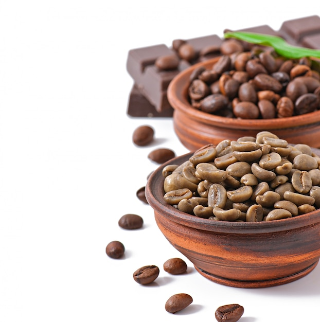 Green and brown coffee beans in bowls Free Photo