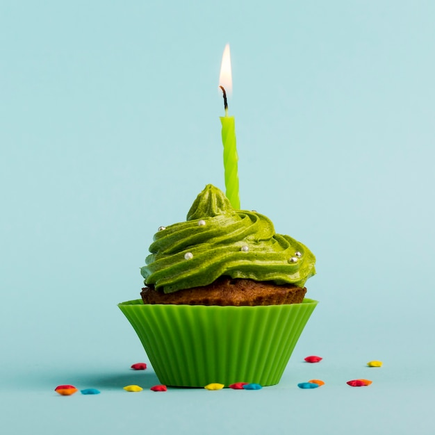 Green burning candles on decorative muffins with colorful star sprinkles against blue backdrop Free Photo